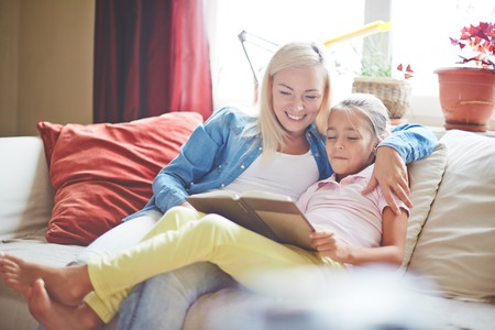 young: Pretty woman and little girl reading book at home Stock Photo