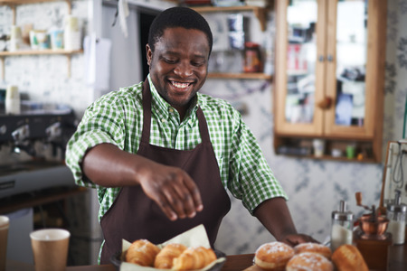 baker: Happy baker powdering buns with vanilla sugar