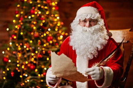 letter writing: Senior man in costume of Santa Claus writing Christmas letter Stock Photo
