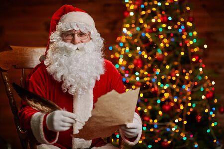 Vrolijke Kerstman met papier en veer kijken naar de camera tijdens het schrijven van kerst brief