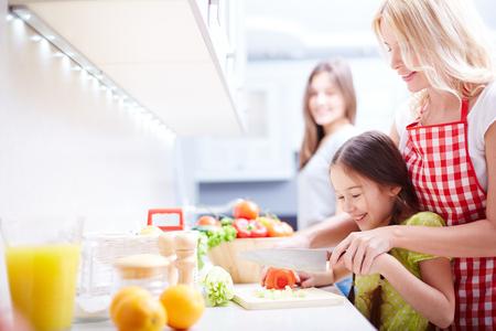 台所でトマトをカット娘を助ける若い女性 写真素材