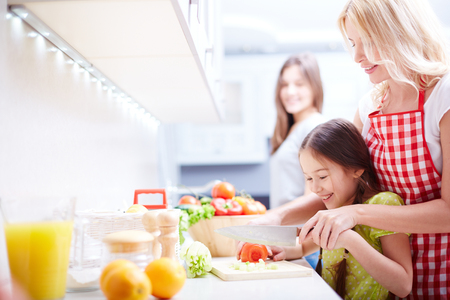 vegetarians: Young woman helping her daughter cut tomato in the kitchen Stock Photo