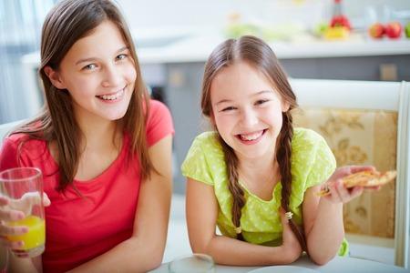 personas comiendo: Dos hermanas que miran la cámara mientras que comer pizza y beber jugo de naranja