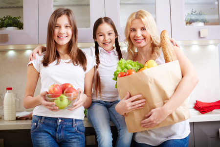 niños felices: Mujer joven y sus hijas mirando a la cámara en la cocina Foto de archivo