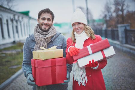 amorous: Amorous dates with giftboxes looking at camera outside
