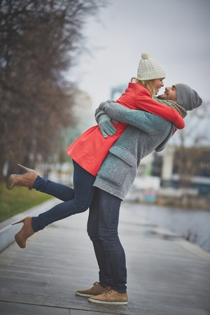 amorous woman: Happy guy holding his girlfriend in urban environment Stock Photo
