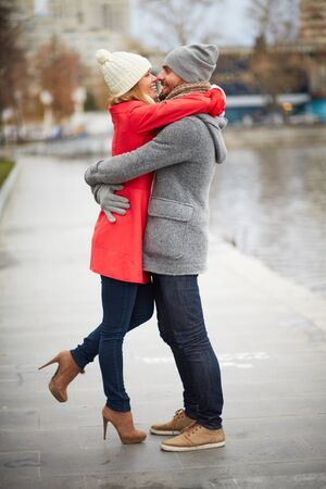 urban environment: Happy guy and his girlfriend embracing in urban environment