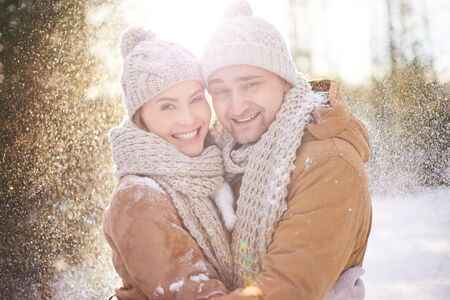 couple dating: Happy couple looking at camera in snowfall