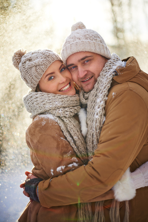 couples hug: Young dates in winterwear looking at camera with smiles