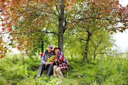 personas mirando: Pareja de ancianos sentados bajo un �rbol en el parque en oto�o