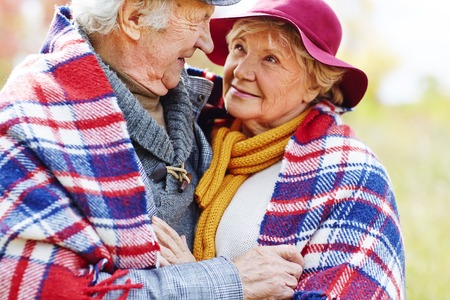 people together: Retired couple in embrace looking at one another Stock Photo