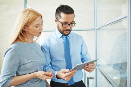 executive woman: Two confident colleagues with touchpad looking at data at meeting