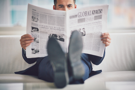 the news: Serious businessman reading newspaper in office