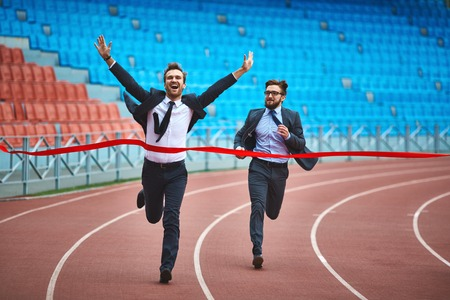 Happy young businessman winning the race