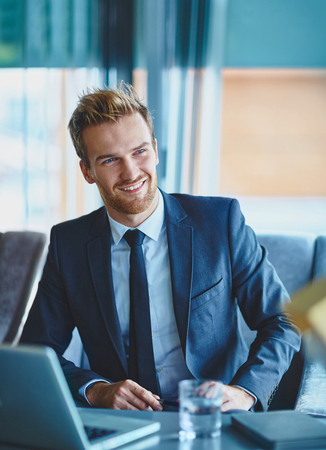 young businessman: Smiling businessman in suit listening to someone