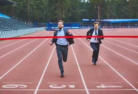 competition: Exitoso hombre de negocios llegando a meta y ganar la competencia