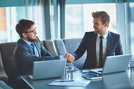 Jonge zakenlieden Handenschudden in bureau na het maken van overeenkomst Stockfoto