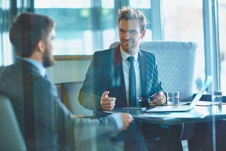 hombre de negocios: Jóvenes empresarios en discusiones sobre los planes de trabajo en la oficina
