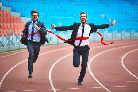 Young businessmen running on stadium