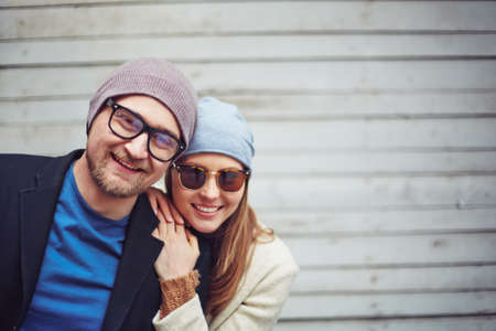 amorous: Amorous couple in stylish casualwear and eyewear looking at camera