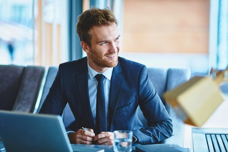 オフィスで座っている笑顔の実業家