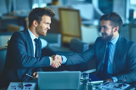 handshaking: Successful young businessmen handshaking at meeting Stock Photo