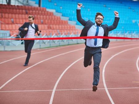 career man: Ecstatic businessman touching red finish ribbon at stadium Stock Photo