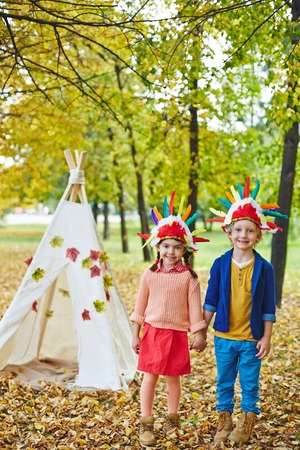 headdresses: Happy girl and boy in Indian headdresses playing in autumn park Stock Photo