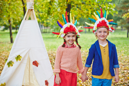 headdresses: Adolescent friends in Indian headdresses looking at camera outdoors