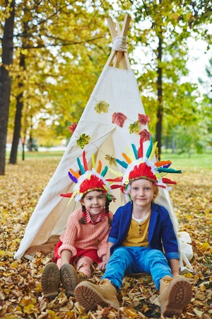 headdresses: Two friendly kids in Indian headdresses looking at camera while sitting on the ground by wigwam