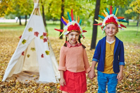 headdresses: Little girl and boy in Indian headdresses looking at camera in autumn park