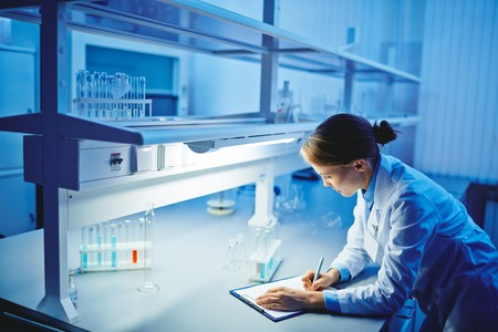 person writing: Female microbiologist making notes in laboratory