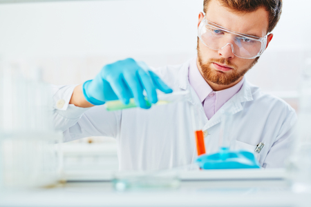Male chemist mixing up liquid substances in laboratory Stock Photo