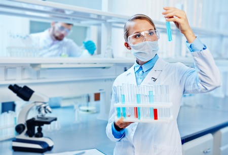 Young chemist analyzing liquids in lab on background of colleague