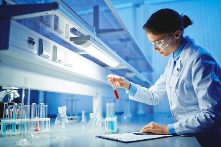 medicamento: Mujer joven que trabaja con líquidos en la cristalería