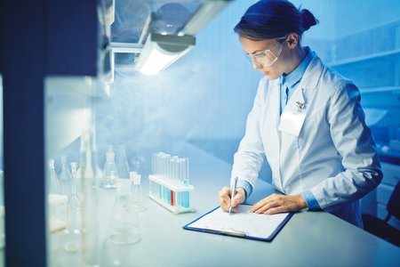 adult writing: Female microbiologist learning characteristics of new substances in laboratory