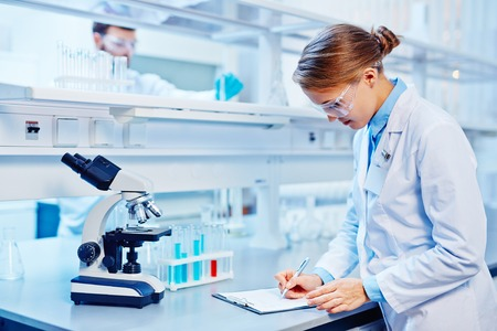 Female chemist making notes in lab on background of colleague