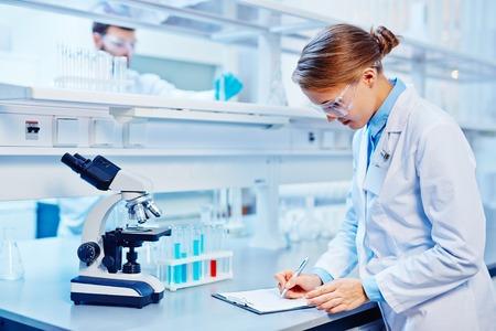 laboratorio: Químico de sexo femenino que hace notas en el laboratorio en el fondo de su colega