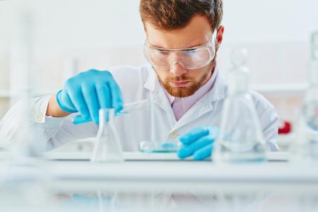 mezclar líquidos en el laboratorio Químico joven Foto de archivo