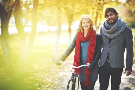 bicycle walk: Romantic couple with bicycle spending weekend in autumn park Stock Photo