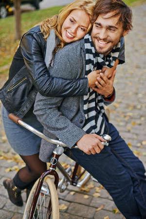 amorous: Young amorous girl embracing her boyfriend on bicycle outside