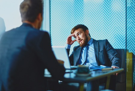 beard man: Handsome employee thinking of idea during talk with his colleague