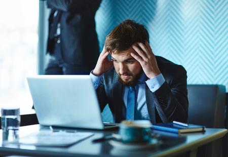 confundido: Hombre de negocios confuso que mira la pantalla de la computadora portátil en el fondo de su colega Foto de archivo
