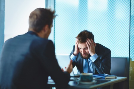 colleague: Male employee touching head while listening to his colleague at meeting