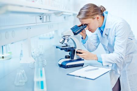 Científico joven que estudia nueva sustancia o virus en el microscopio