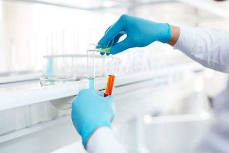 gloved: Gloved hands of chemist mixing up fluids
