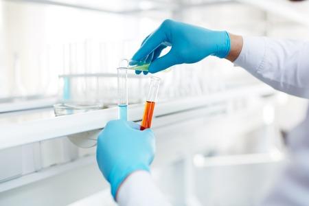 investigando: Manos con guantes de farmacia mezclar fluidos