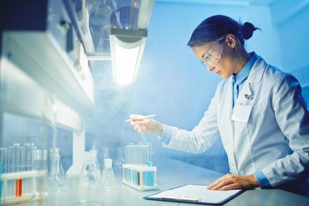 Jonge assistent werken met chemische vloeistoffen in flesjes