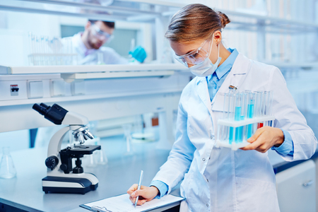 Young woman with flasks making notes in laboratory