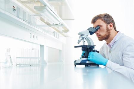 Jonge wetenschapper onderzoekt microbiologische stof in microscoop Stockfoto